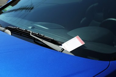Parking violation ticket on car windshield, closeup