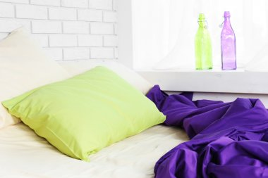 Comfortable bed with purple blanket
