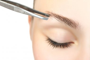 woman plucking eyebrows with tweezers