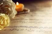 Fotografie schöne Rosen mit Perlen und Kerze auf Notenblättern Hintergrund