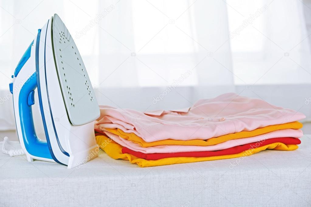 Elektronische strijken en stapel van kleding — Stockfoto ...