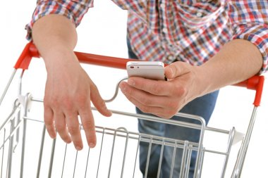 man holding phone and shopping cart
