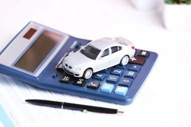 Toy car, documents and calculator on table. Car insurance concept