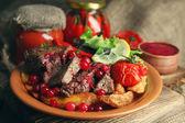 chutné pečené maso s brusinkovou omáčkou, salát a pečené zeleniny na talíři, na dřevěné pozadí