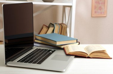 Laptop with books on table
