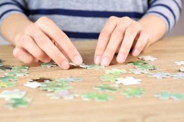 Female hands assembling puzzle
