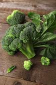 Čerstvé brokolice s listovým špenátem na dřevěný stůl zblízka