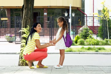 school girl with mother walking