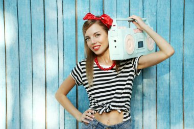 Beautiful girl with pretty smile holding retro tape recorder on color wooden background