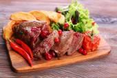 manzo con cranberry salsa, fette di patata arrostita sul tagliere, su fondo di legno