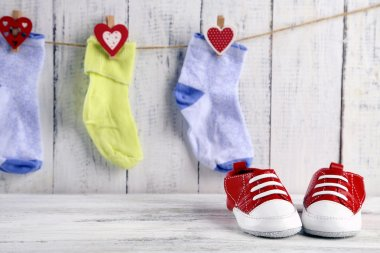 Cute toddler shoes and socks on wooden background
