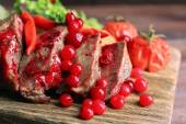 hovězí maso s brusinkovou omáčkou, opečené bramborové plátky na prkénko, na dřevěné pozadí