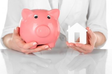 Woman holding model of house and piggy bank close up