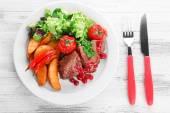 chutné pečené maso s brusinkovou omáčkou a restovanou zeleninou na desce, na barevné dřevěné pozadí
