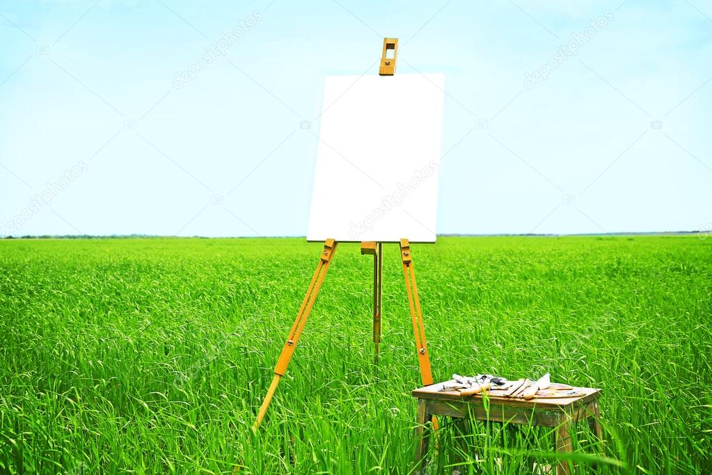 Easel with canvas in field