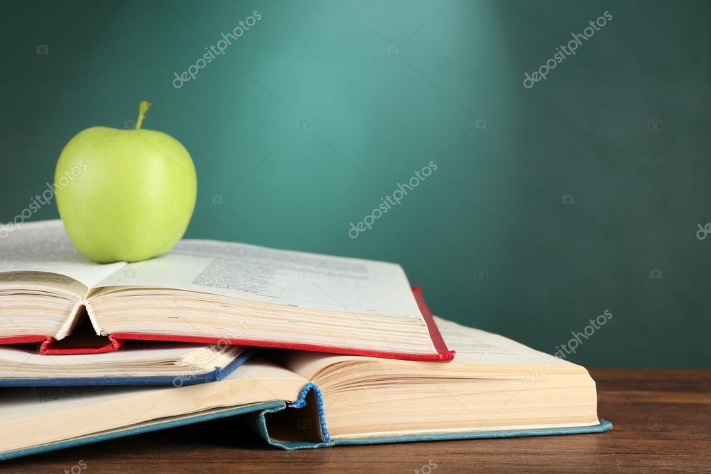 Open Books And Green Apple On Desk Chalkboard Background Stock Photo