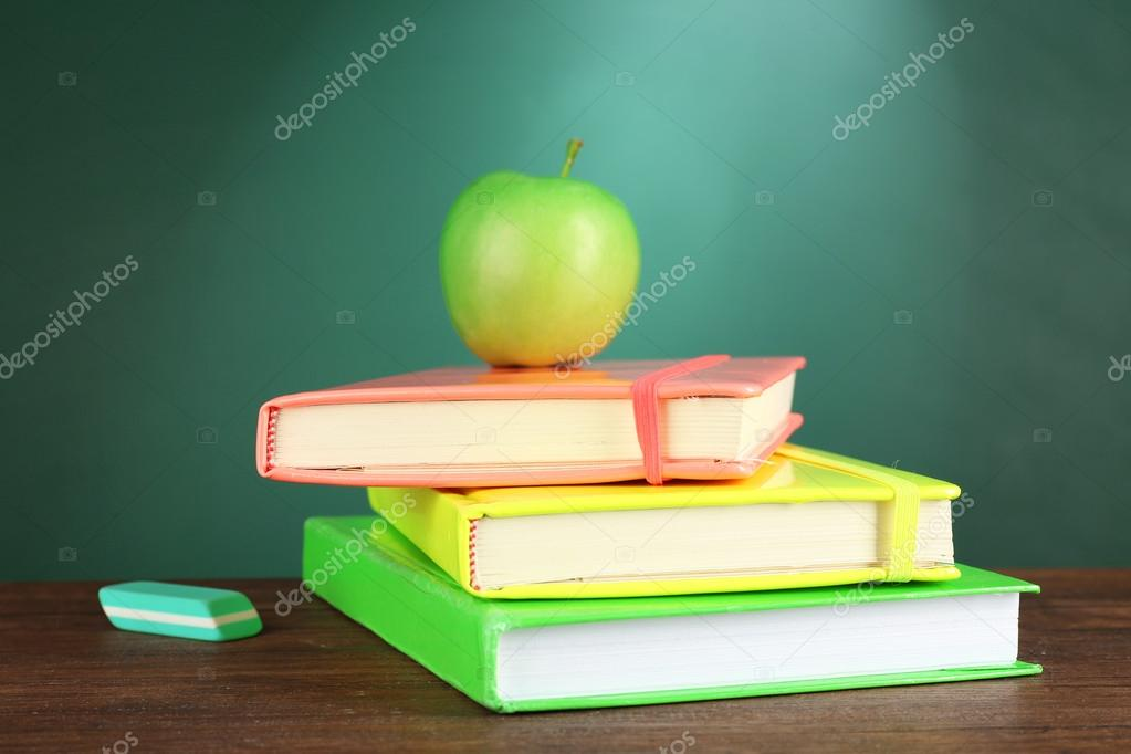 Stack Of Books With Green Apple And Eraser On Desk Chalkboard Background Stock