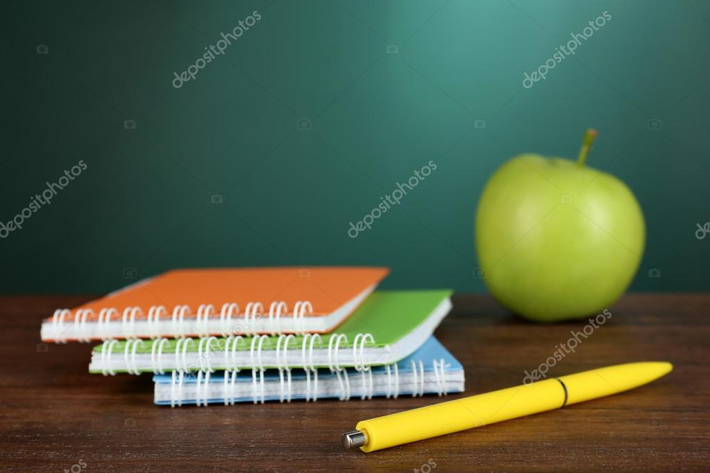 Colorful Notebooks With Pen And Green Apple On Desk Chalkboard Background Photo By Belchonock