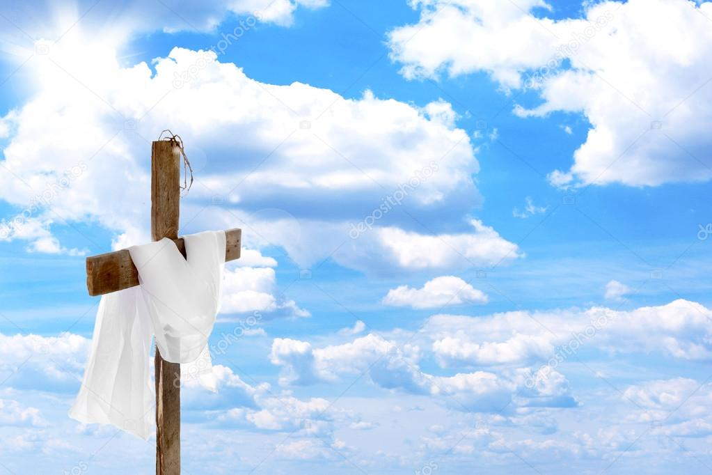 Cross with crown of thorns and cloth, on blue sky background