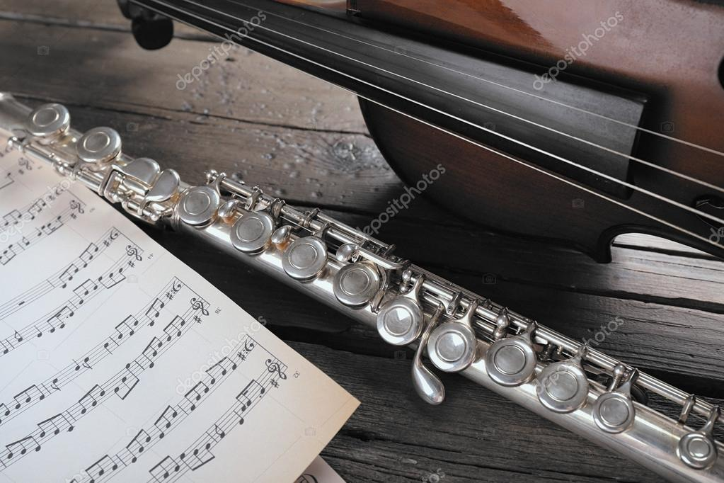Flute and violin with music notes on wooden table close up — Stock
