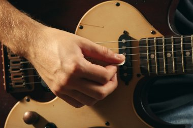 Young musician playing electric guitar close up