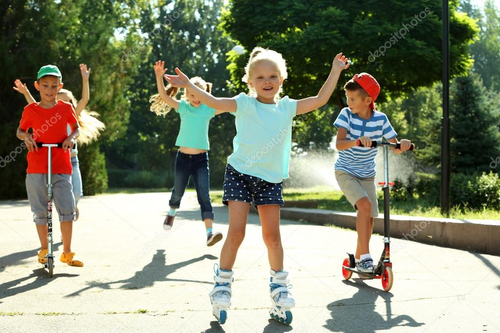 Children riding on scooters and roller skates in park