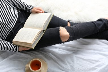 Woman on the bed with old book and cup of coffee