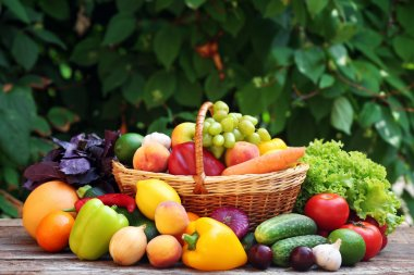 Heap of fresh fruits and vegetables in basket on table outdoors
