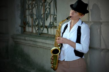 Girl with saxophone outside