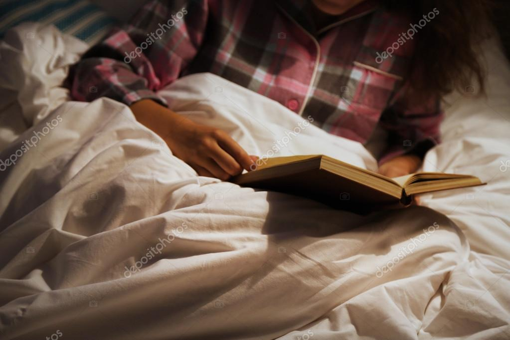 woman reading book in bad