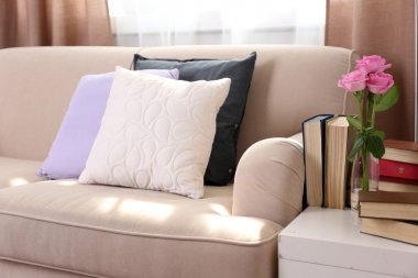 Comfortable sofa with pillows and table with books near it in the room, close up