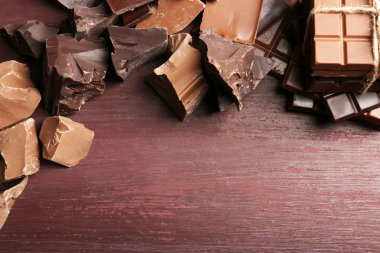 Variety of chocolate pieces on wooden background