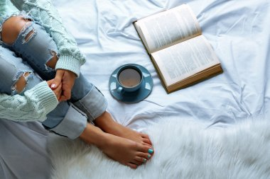 Woman on the bed with old book and cup of coffee, top view point
