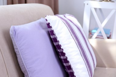Pastel color room interior with comfortable sofa and pillows, close up