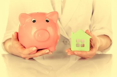 Woman holding house and piggy bank