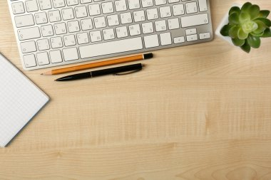 White keyboard and notebook on the desk