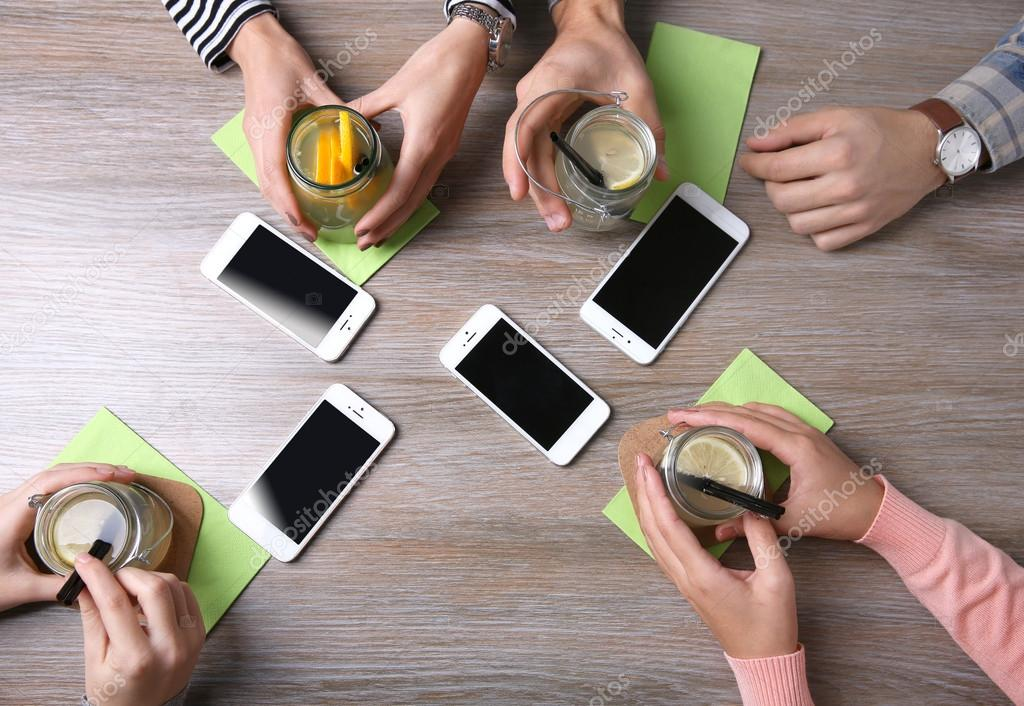 Four hands with smart phones