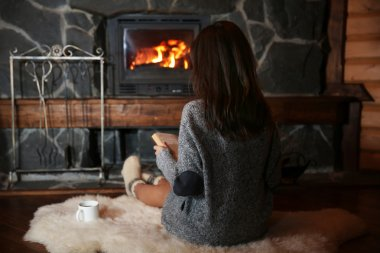 Woman with cup and book near fireplace
