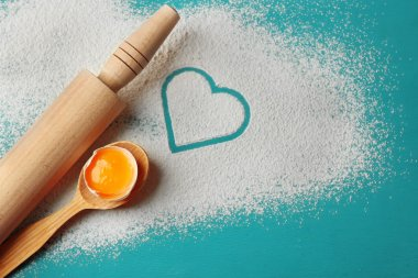 Hearts of flour and rolling pin, wooden spoon on color wooden background