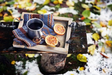 Tray with mug of mulled wine on Old wooden bench in mountains