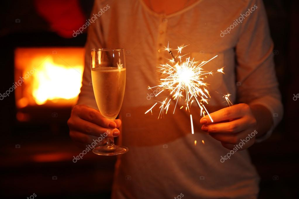 Female hands with sparkler and glass of sparkle wine on fireplace ... : fireplace background : Fireplace Design