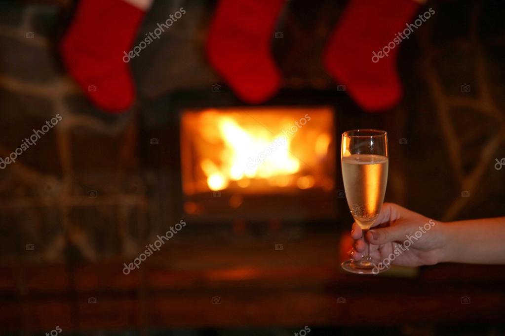 Fireplace Design fireplace background : Female hand with glass of sparkle wine on fireplace background ...