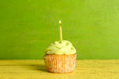 Tasty cupcake with candle on yellow wooden table against green background