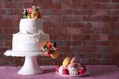 Schöne Hochzeitstorte, dekoriert mit Blumen und Platte mit Kuchen auf Rosa Tisch vor Ziegel-Wand-Hintergrund