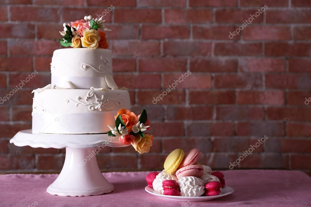 Beautiful wedding cake decorated with flowers and plate with cakes on pink table against brick wall background u2014 Photo by belchonock & Beautiful wedding cake decorated with flowers and plate with cakes ...