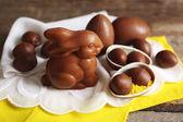 Fotografie Schoko-Osterhasen und Eier auf hölzernen Hintergrund