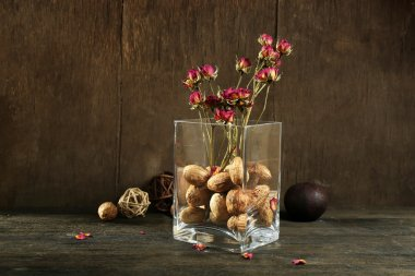 Composition of nuts, wooden balls and stale flowers