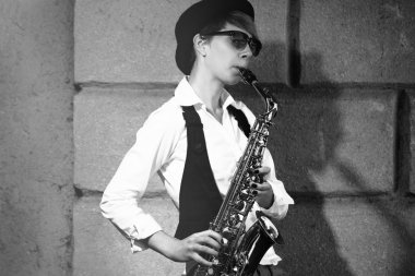 Attractive woman playing saxophone
