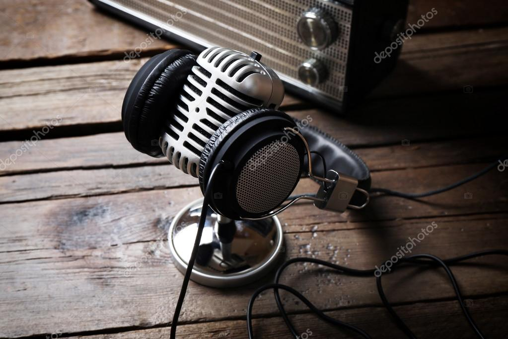 Microphone with headphones and radio on wooden background