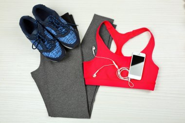 Sport clothes, shoes  and smart phone with earphones on light background
